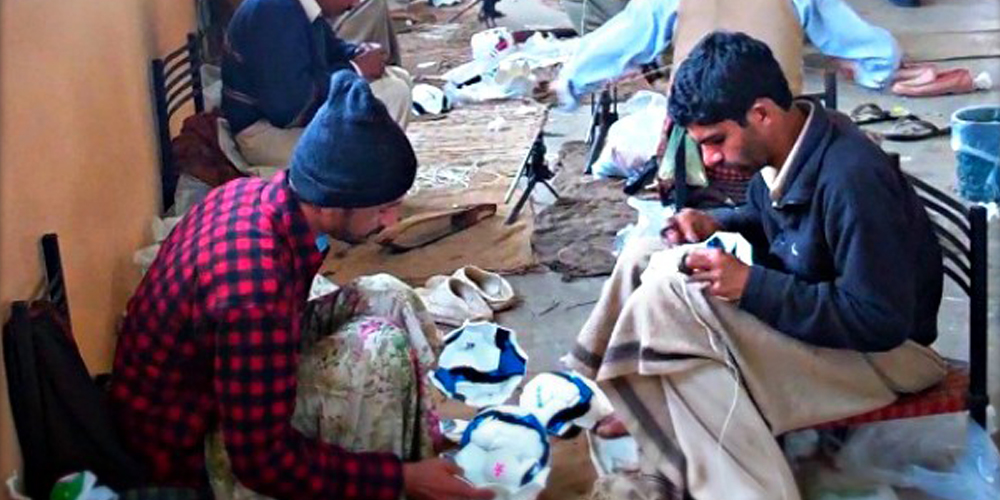men sewing footballs